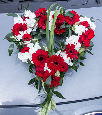 Car jewelry with red gerbera and roses on a bonnet for the wedding. Copy space