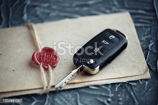 936987338 istock photo car key and envelope on the desk 1204891057