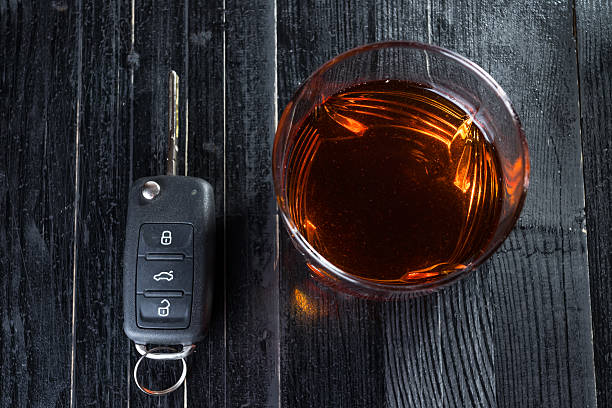 car key and whiskey in a glass on black wooden - whisky test stock-fotos und bilder
