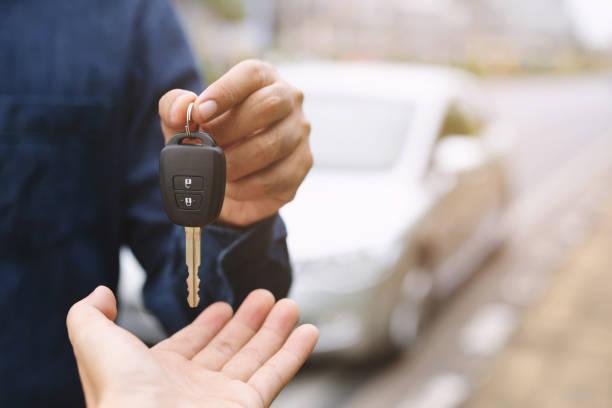 chiave dell'auto, l'uomo d'affari che consegna dà la chiave dell'auto all'altra donna sullo sfondo dell'auto. - auto foto e immagini stock