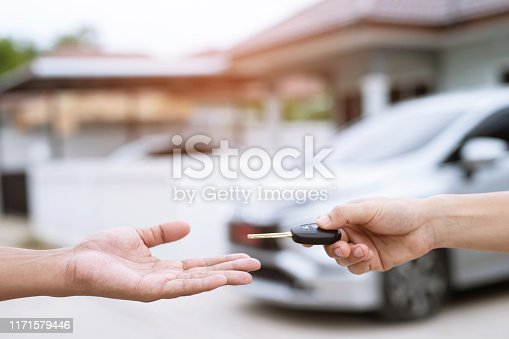 939005154 istock photo Car key, businessman handing over gives the car key to the other woman on behind the new car background. transportation and vehicle concept. 1171579446