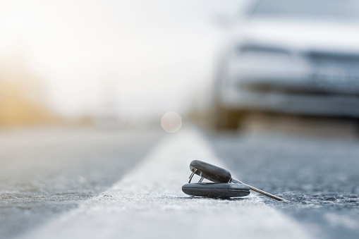 Car key fall on the asphalt road. Driver lost his vehicle keys and walks away. Misfortune concept. Blurred foreground and background with bokeh effect