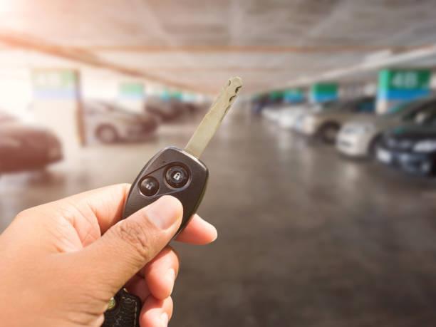 Autoschlüssel in der Hand am Parkplatz Auto Hintergrund – Foto