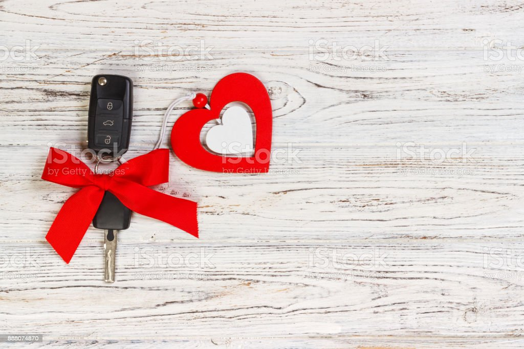 Car key with a red ribbon adn a heart on white wooden table. Giving present or gift for valentine's day or christmas stock photo