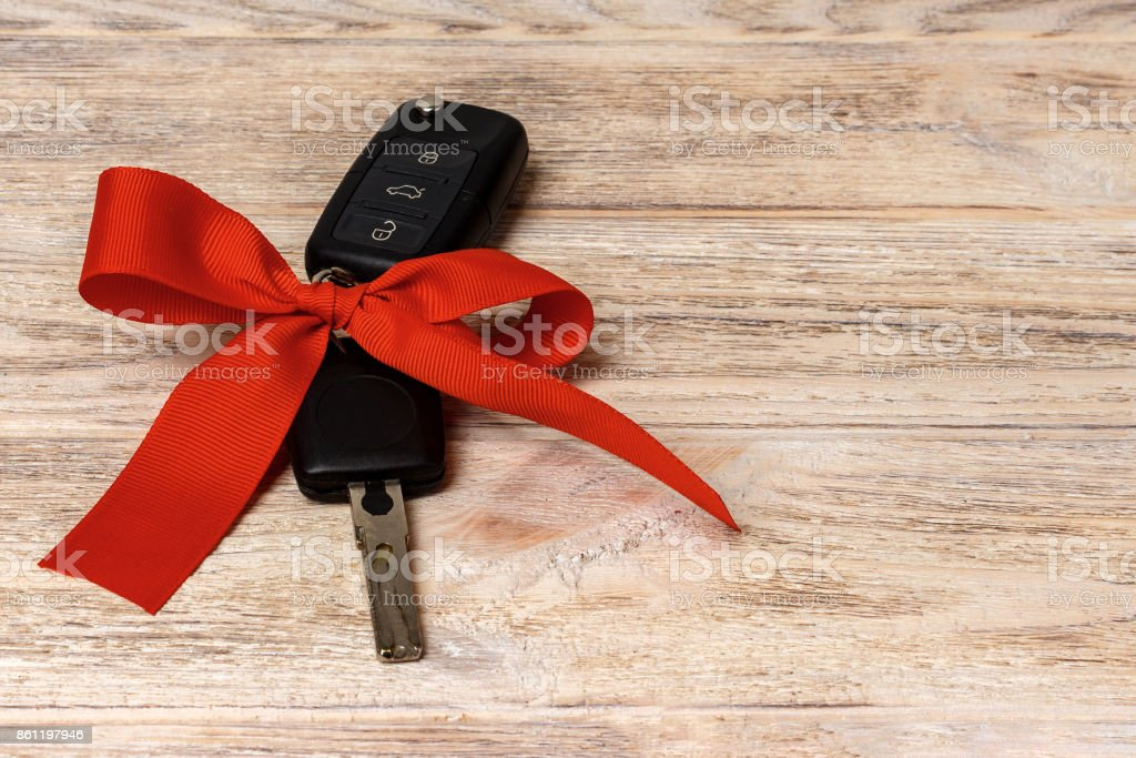 Car key with colorful bow on wooden background stock photo