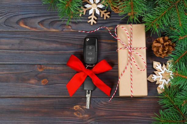 fahrzeugschlüssel mit bunten bogen mit geschenk-box auf hölzernen hintergrund - autoschleifen stock-fotos und bilder