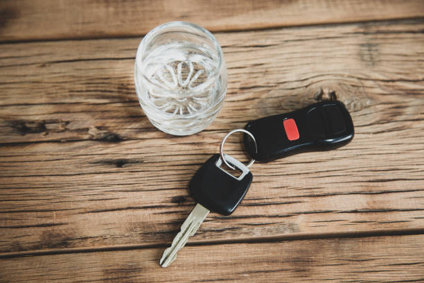 car key with glass of vodka on desk stock photo