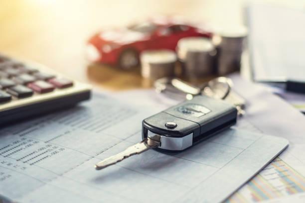 Fahrzeugschlüssel mit Geld und Rechner auf Tabelle. Konzept-Finanzen und Versicherungen – Foto