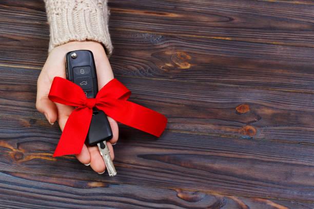 fahrzeugschlüssel mit roter schleife in woomen hand auf hölzernen hintergrund. valentinstag-konzept - autoschleifen stock-fotos und bilder
