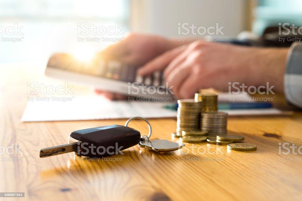 Las llaves del coche y dinero en mesa con hombre usando calculadora. - foto de stock