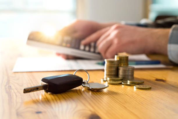 Car keys and money on table with man using calculator. stock photo