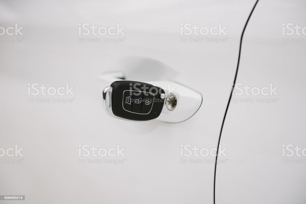 Car keys in white door lock closeup with copy space stock photo