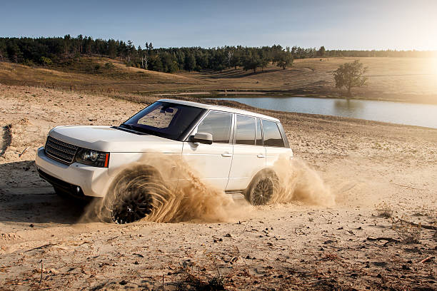 Car Land Rover Range Rover dirty sand burnout drive off-road Saratov, Russia - September 1, 2014: Land Rover Range Rover car drive at countryside sand road near pond at daytime range rover stock pictures, royalty-free photos & images