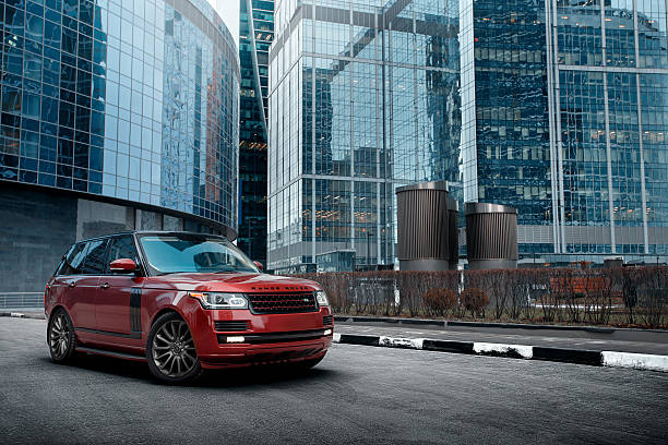 Car Land Rover Range Rover in the city at daytime Moscow, Russia - November 22, 2015: Premium car Land Rover Range Rover standing near modern building in the city at daytime range rover stock pictures, royalty-free photos & images