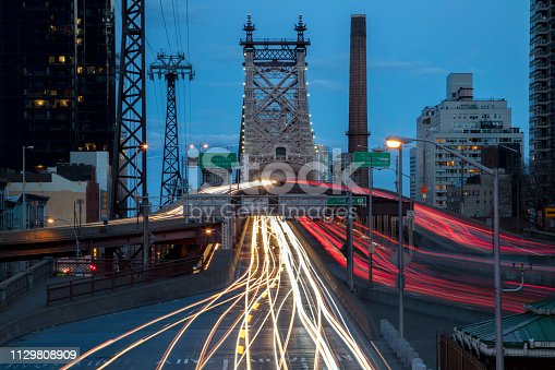 Car light trails from traffic in E 59th St & 2nd Avenue and over the Queensboro Bridge at dusk, Midtown Manhattan, New York City.