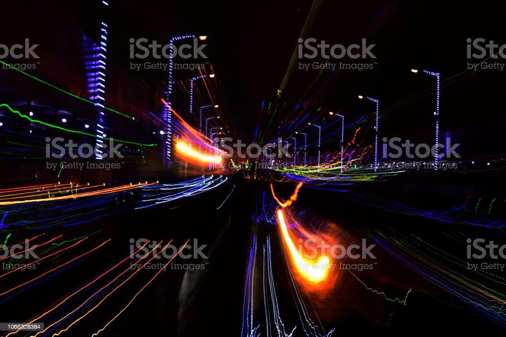 Motion blur car light trails on highway against black background.