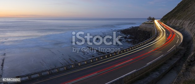 istock Car lights at night by the sea, Zumaia, Basque Country 628803550