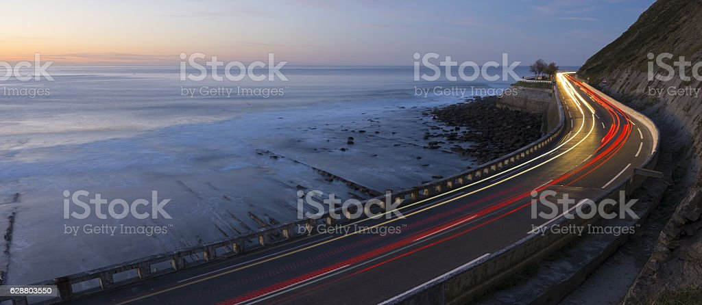 Car lights at night by the sea, Zumaia, Basque Country stock photo