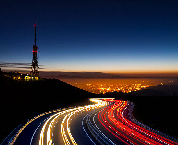 car lights at night towards the city and communications antenna stock photo