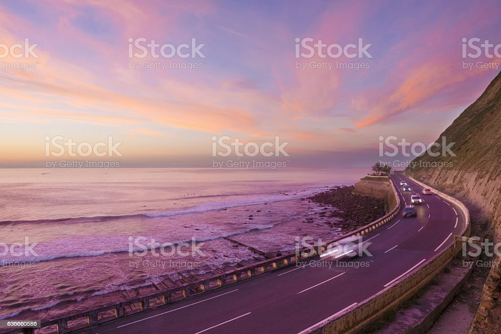 Car lights at sunset by the sea, Zumaia, Basque Country stock photo