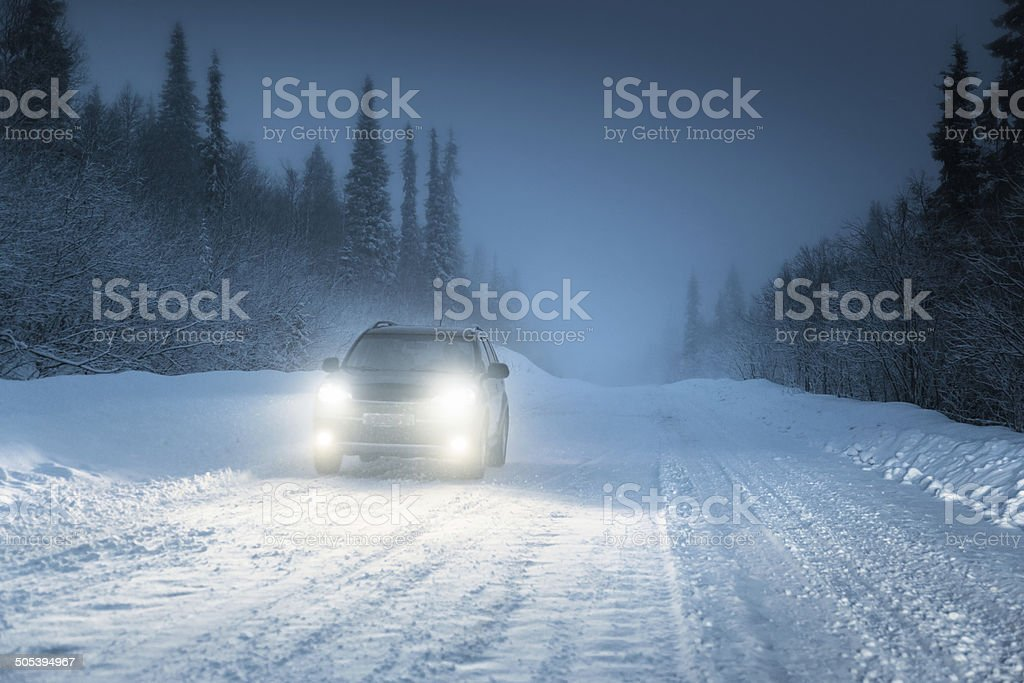 Car lights in winter Russian forest stock photo