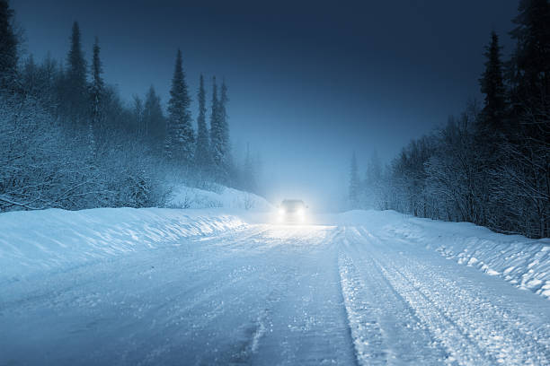 car lights in winter russian forest - mist donker auto stockfoto's en -beelden