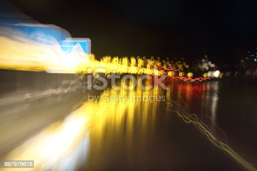 istock Car lights on the streets at night and blurry. 697979618