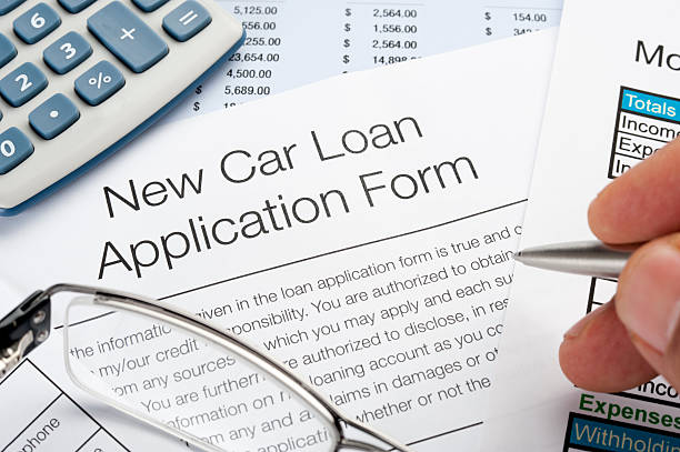 Car loan application Form with pen, calculator, writing hand stock photo