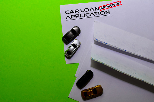 istock Car Loan Application in Approved with post card on office desk background 1192767308
