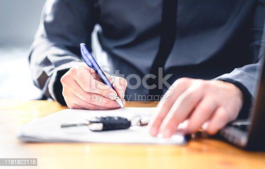 istock Car loan form or lease application document. Man signing paper contract to sell premium vehicle. Buyer or dealer in agency. Auto insurance or finance paperwork. 1181822115
