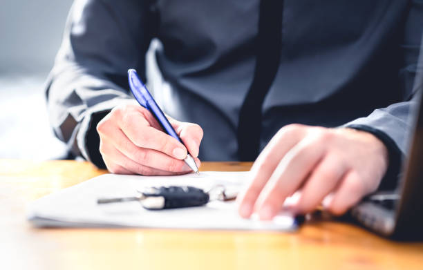 Car loan form or lease application document. Man signing paper contract to sell premium vehicle. Buyer or dealer in agency. Auto insurance or finance paperwork. stock photo