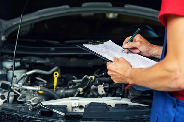 autowartung und -reparatur - mechaniker schreiben checklistenpapier auf zwischenablage - autowerkstatt stock-fotos und bilder