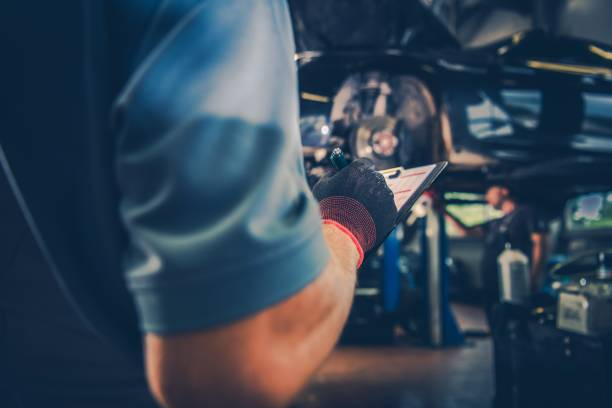 Car Maintenance Check List Vehicle Maintenance Check List. Car Mechanic with Documentation in Hand. Automotive Industry Theme. auto repair shop stock pictures, royalty-free photos & images