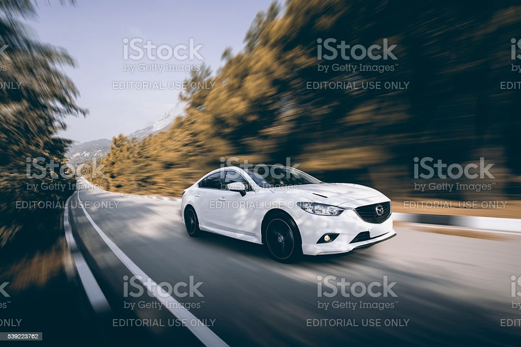 Car Mazda driving on road at daytime stock photo