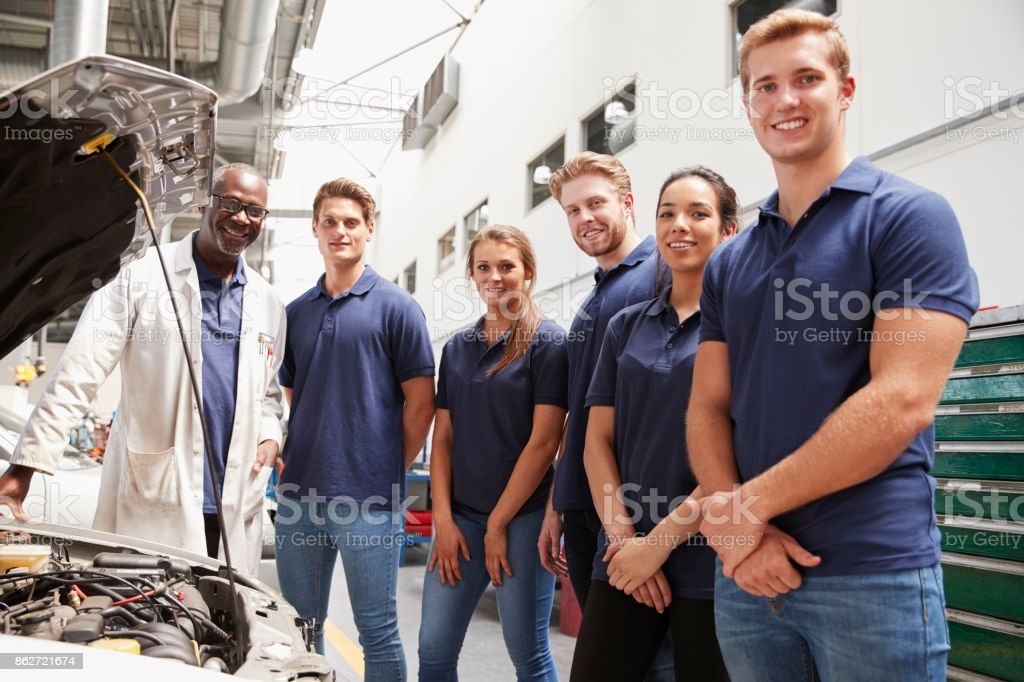 Car mechanic and apprentices in a garage looking to camera stock photo