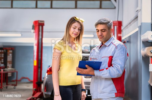 136591855 istock photo Car Mechanic and Customer Document Examining in the Auto Repair Shop 1185827623