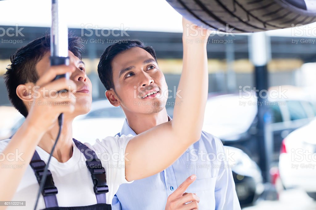Car mechanic and customer in Asian auto workshop stock photo
