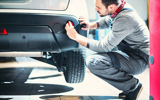 Car mechanic at work. Closeup of mid 30's male car mechanic kneeling next to rear bumper of the vehicle and installing red reflector after replacing a bumper. The car is slightly lifted. Side view. bumper stock pictures, royalty-free photos & images