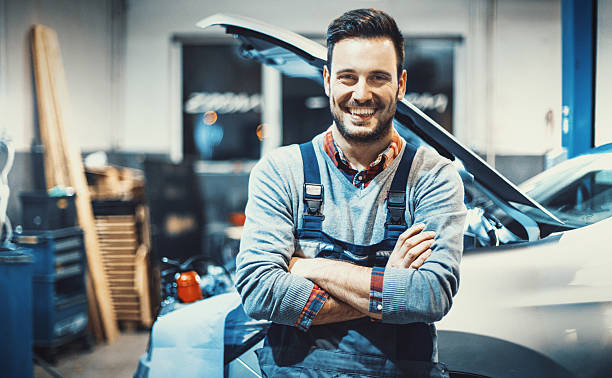 Car mechanic at work. Closeup front view portrait of smiling handsome mechanic standing in front of a car with his arms folded, smiling and looking at camera. mechanic stock pictures, royalty-free photos & images