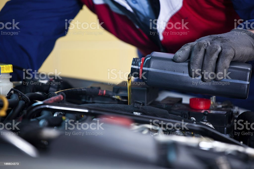 Car mechanic changing engine oil royalty-free stock photo
