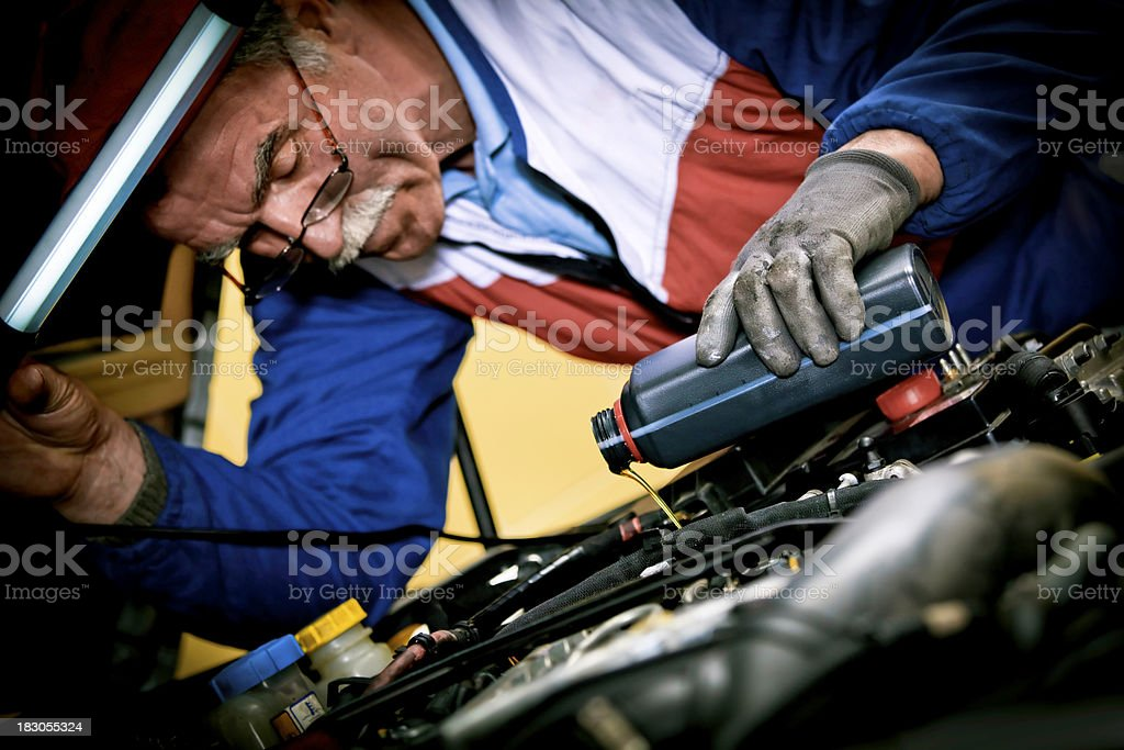 Car mechanic changing oil royalty-free stock photo