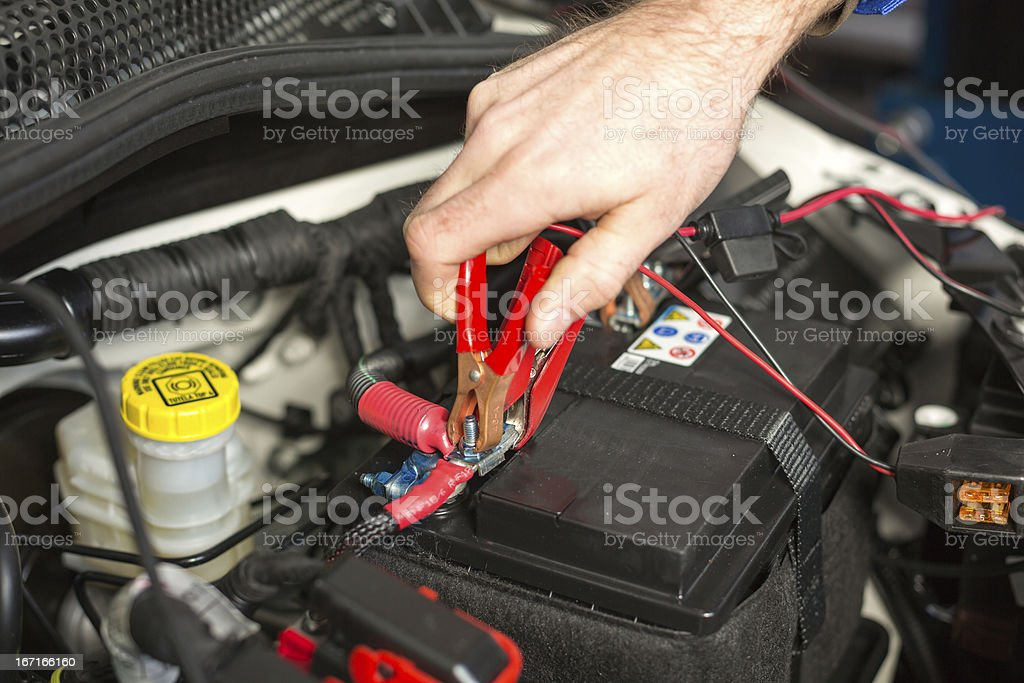 Car mechanic changing the battery royalty-free stock photo