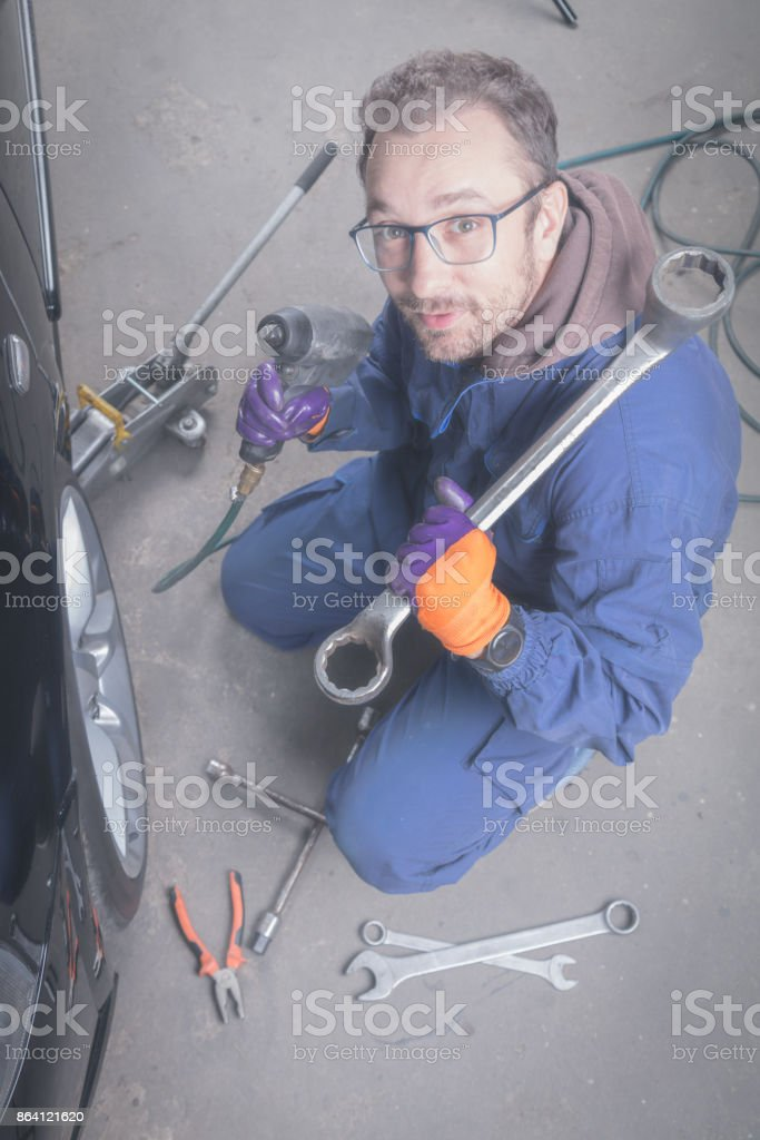 Car mechanic changing tire in the service - shop. royalty-free stock photo