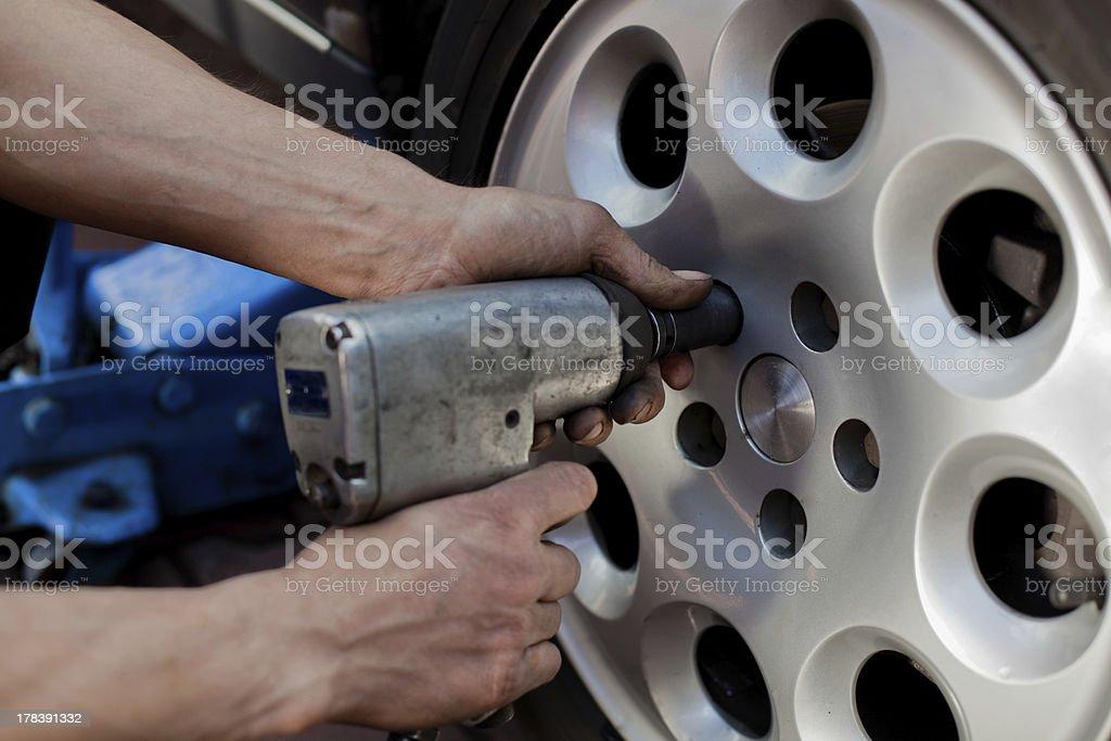 Car mechanic changing wheel royalty-free stock photo