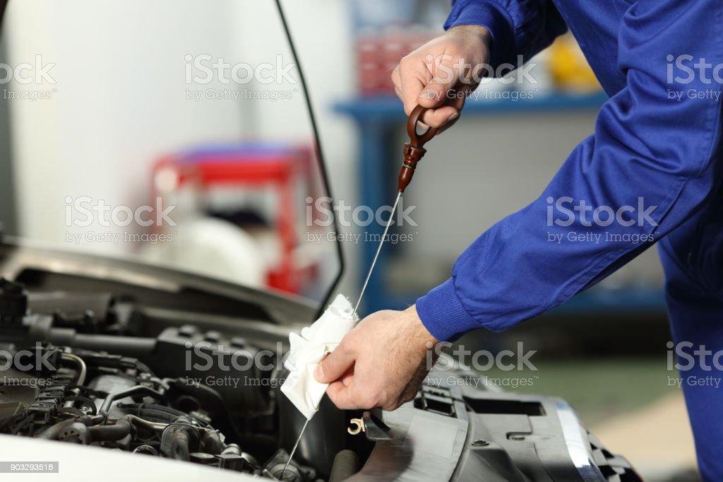 Car mechanic checking oil level stock photo