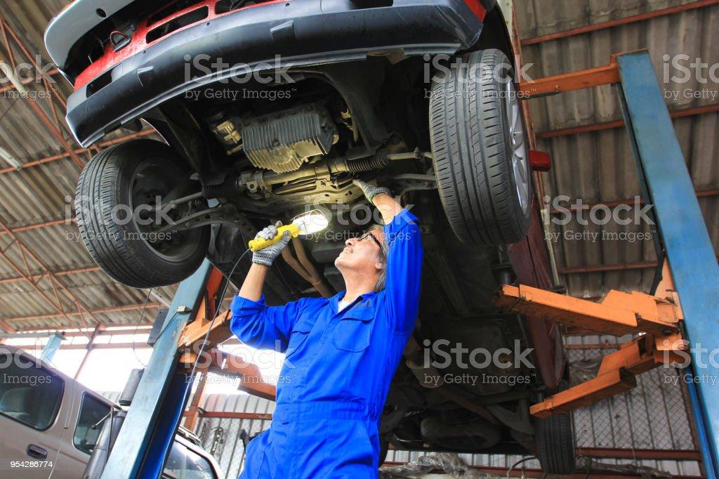car mechanic examining car using flashlight in auto repair service