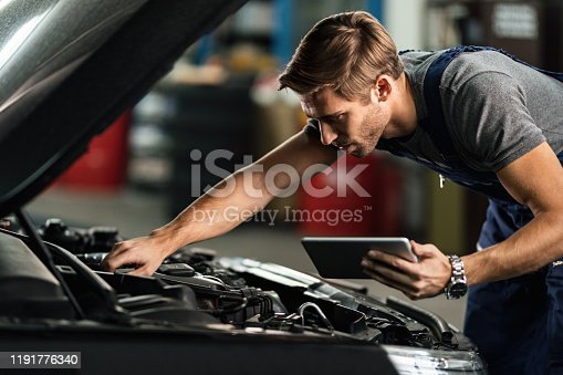 1137474295 istock photo Car mechanic examining engine malfunction while using touchpad in auto repair shop. 1191776340