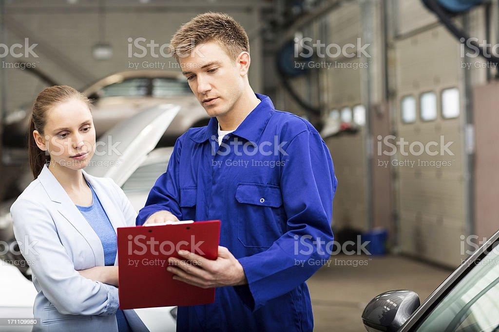 Car Mechanic Explaining Auto Repair Estimates royalty-free stock photo