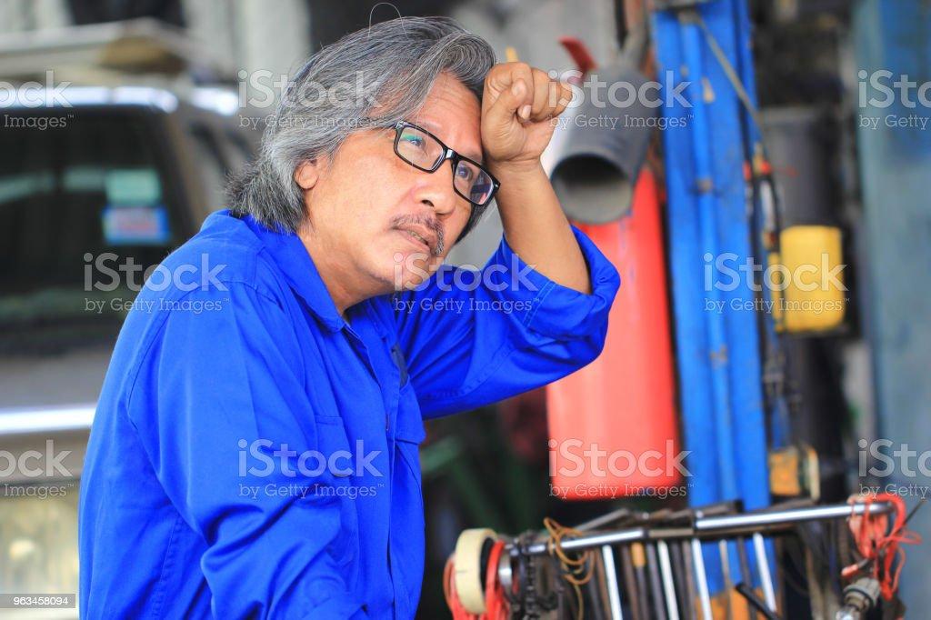 Mechanik samochodowy czuje się smutny i męczący po pracy w serwisie samochodowym. - Zbiór zdjęć royalty-free (Bezpieczeństwo)