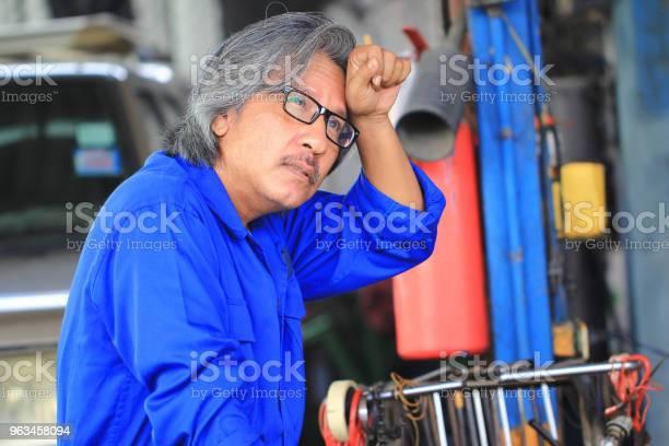 Mechanik Samochodowy Czuje Się Smutny I Męczący Po Pracy W Serwisie Samochodowym - zdjęcia stockowe i więcej obrazów Bezpieczeństwo
